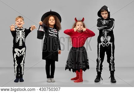 halloween, holiday and trick-or-treating concept - smiling children in carnival costumes making faces and playing trick or treat game over grey background