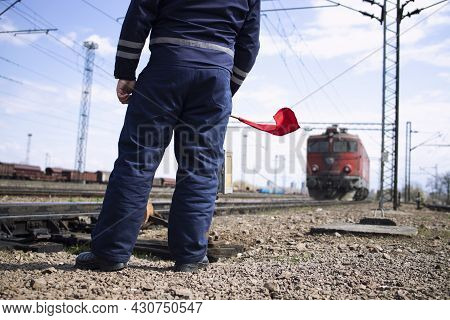 Railroader Or Switchman At Station Waving With Red Flag To The Incoming Train And Signalizing Locomo