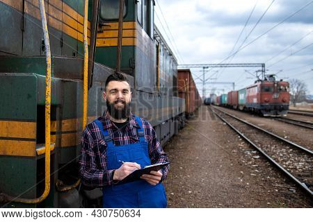 Portrait Of Engine Train Driver Standing By Locomotive At Train Station And Holding Departure Schedu