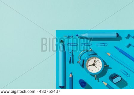 Top View Photo Of Ordered School Supplies Blue Stationery Felt Pens Pencils Clips Pushpins And Alarm