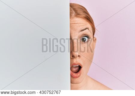 Young irish woman holding blank empty banner showing half face afraid and shocked with surprise and amazed expression, fear and excited face.