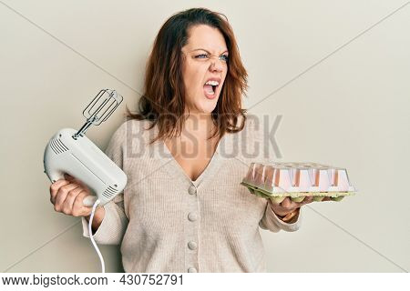 Young caucasian woman holding pastry blender electric mixer and eggs angry and mad screaming frustrated and furious, shouting with anger. rage and aggressive concept.