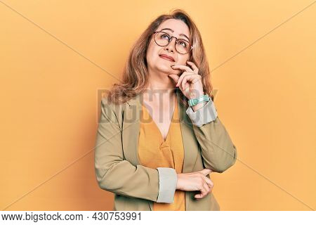 Middle age caucasian woman wearing casual clothes serious face thinking about question with hand on chin, thoughtful about confusing idea