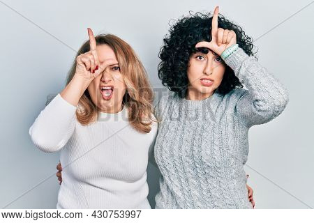 Middle east mother and daughter wearing casual clothes making fun of people with fingers on forehead doing loser gesture mocking and insulting.