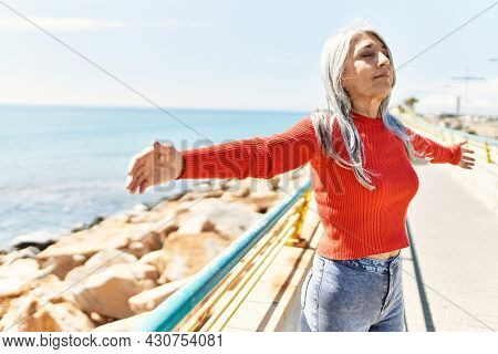 Middle age grey-haired woman breathing with arms open standing at the beach.