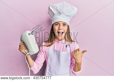 Beautiful brunette little girl wearing chef hat holding pastry blender electric mixer pointing thumb up to the side smiling happy with open mouth