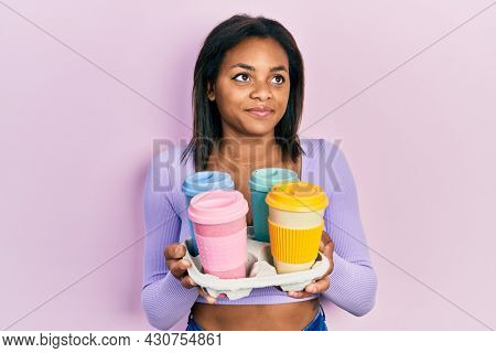 Young african american girl holding tray with take away coffee smiling looking to the side and staring away thinking.