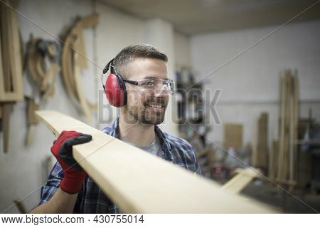 Portrait Of Middle Aged Blonde Carpenter With Eyes And Ears Protection Carrying Wooden Plank In Wood