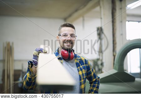 Carpenter Holding Wood Plank In Woodworking Workshop.