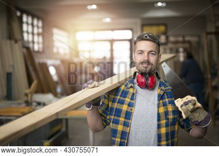Portrait Of Professional Middle Aged Carpenter With Wood Plank And Tools Standing In His Woodworking