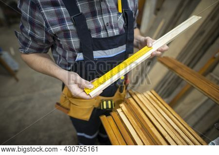 Unrecognizable Carpenter Taking Measurements Of The Plank He Is About To Cut In Woodworking Workshop