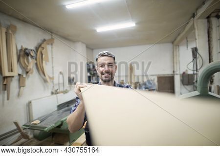 Professional Carpenter Holding Plank In Woodworking Workshop.