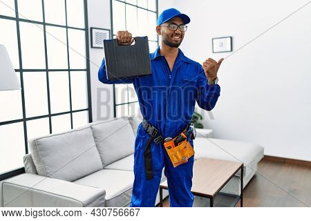 Young indian technician holding toolbox and screwdriver at house pointing thumb up to the side smiling happy with open mouth