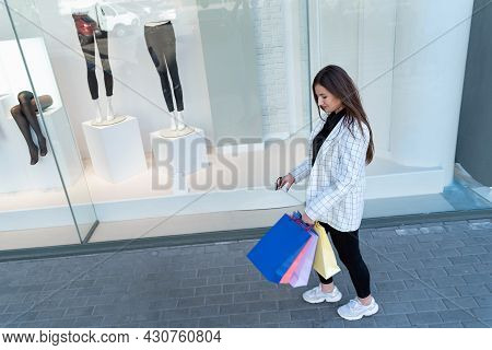 Girl After Successful Shopping Is Holding Multi-colored Shopping Bags. Shopaholic. Showcase On Backg