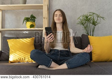 Girl Turned On Mantra On Phone And Meditating. Woman Sits In Lotus Position And Turns On Meditation