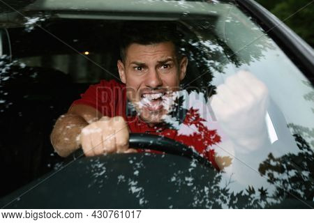Stressed Man In Driver's Seat Of Modern Car, View Through Windshield
