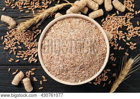 Bowl Of Wheat Bran On Black Wooden Table, Flat Lay
