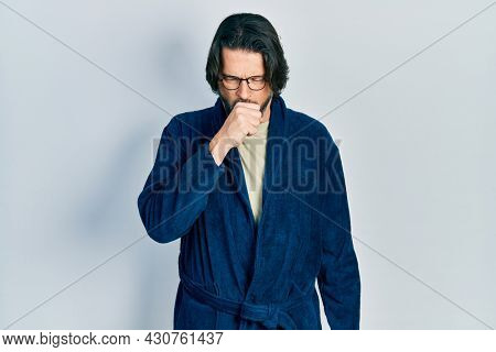 Middle age caucasian man wearing bathrobe and glasses feeling unwell and coughing as symptom for cold or bronchitis. health care concept.