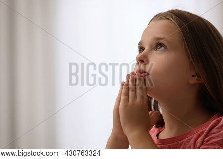 Cute Little Girl With Hands Clasped Together Praying On Blurred Background. Space For Text