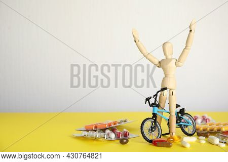 Pills, Sportsman And Bike Model On Yellow Table, Space For Text. Using Doping In Cycling Sport Conce