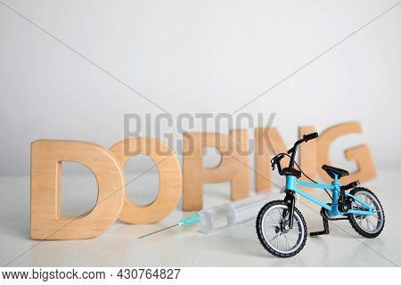 Word Doping, Syringe And Bicycle Model On Light Background