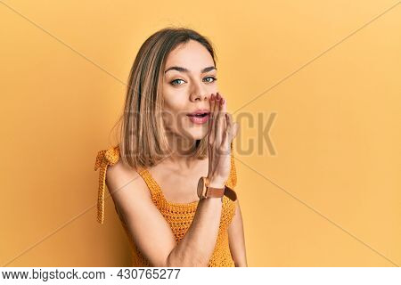 Young caucasian blonde woman wearing casual yellow t shirt hand on mouth telling secret rumor, whispering malicious talk conversation