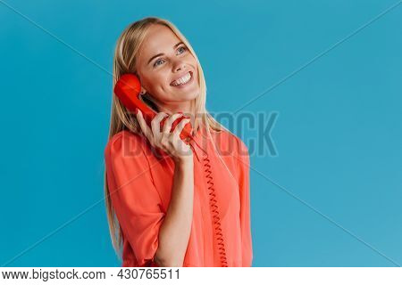 Smiling young blonde woman with long hair standing over blue background calling on a landline phone