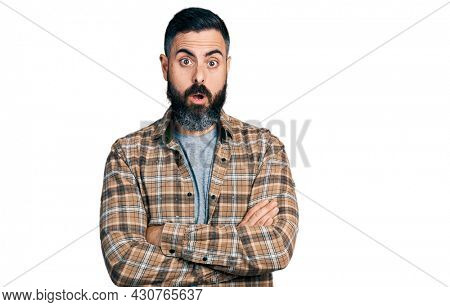 Hispanic man with beard with arms crossed gesture afraid and shocked with surprise and amazed expression, fear and excited face.