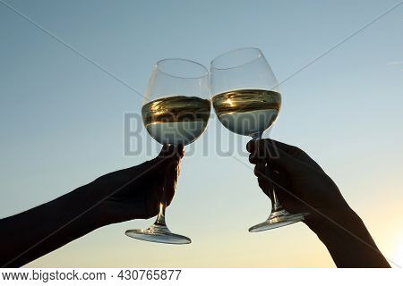 Women Clinking Glasses Of Wine Against Sky At Sunset, Closeup