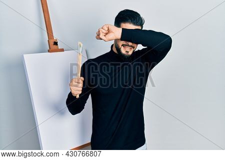 Handsome man with beard holding brushes close to easel stand smiling cheerful playing peek a boo with hands showing face. surprised and exited