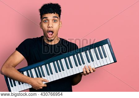 Young african american man holding piano keyboard afraid and shocked with surprise and amazed expression, fear and excited face.