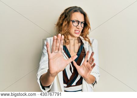 Young caucasian woman wearing business style and glasses disgusted expression, displeased and fearful doing disgust face because aversion reaction. with hands raised