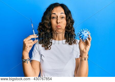 Middle age hispanic woman holding virus toy and syringe puffing cheeks with funny face. mouth inflated with air, catching air.
