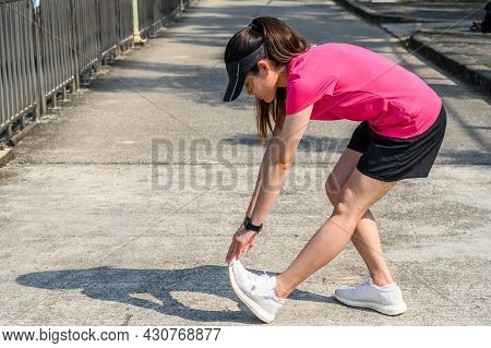 Portrait Of Runner Woman Doing Stretching And Warming Up Her Legs Before Running In The Public Park.