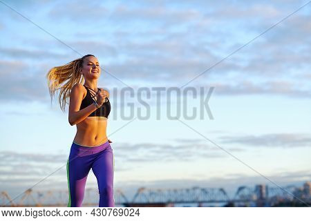 Running Woman At Sunrise. Morning Jogging On The Beach Or Coast Of River On Urban City Background