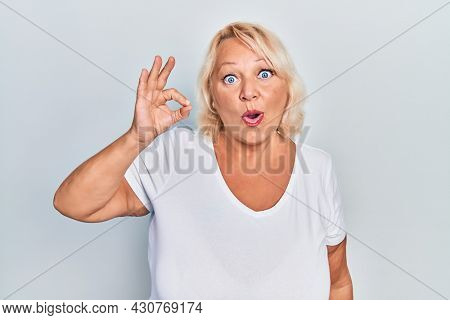Middle age blonde woman doing ok positive gesture afraid and shocked with surprise and amazed expression, fear and excited face.