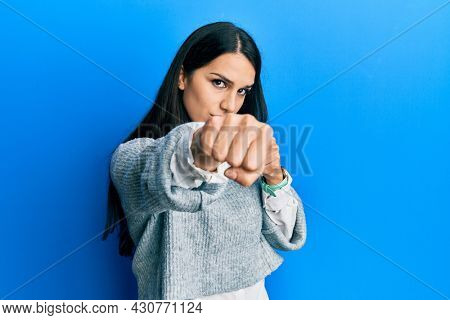 Young hispanic woman wearing casual clothes punching fist to fight, aggressive and angry attack, threat and violence