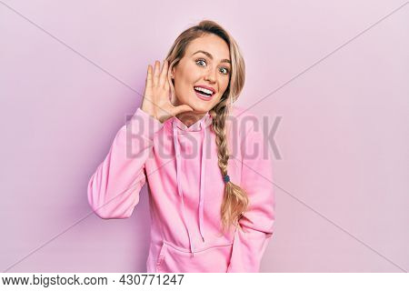 Beautiful young blonde woman wearing pink sweatshirt smiling with hand over ear listening and hearing to rumor or gossip. deafness concept.