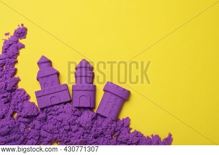 Castles Made Of Kinetic Sand On Yellow Background, Flat Lay. Space For Text