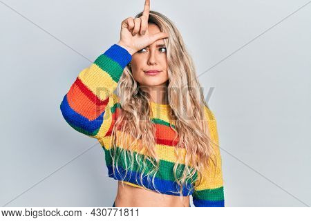 Beautiful young blonde woman wearing colored sweater making fun of people with fingers on forehead doing loser gesture mocking and insulting.