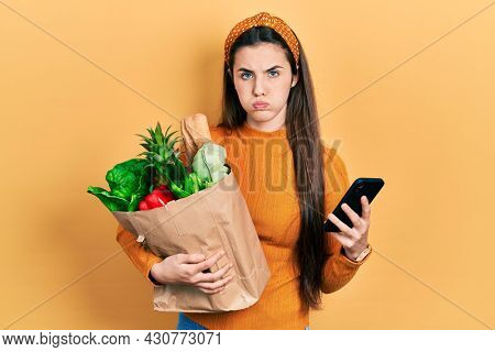 Young brunette teenager holding bag of groceries using smartphone puffing cheeks with funny face. mouth inflated with air, catching air.