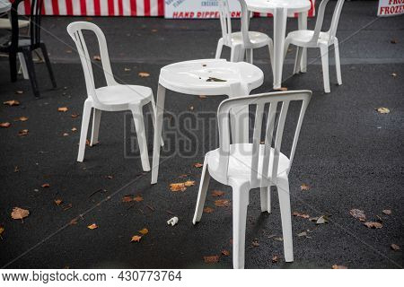 Quaint Village Street Fair Pop Up Restaurant Scene With Wet Cafe Tables On An Asphalt Street. Natura