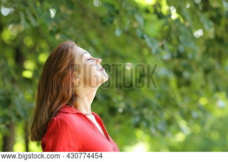 Profile Of A Woman In Red Breathing Fresh Air In A Green Park