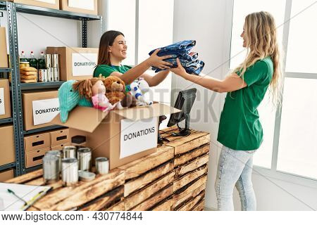 Young volunteer girl helping woman at charity center.
