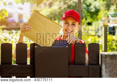 Smiling Postman Mail Carrier Inserting Envelope Into Mailbox