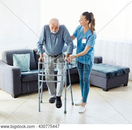 Doctor Or Nurse Caregiver With Senior Man Using Walker Assistanece At Home Or Nursing Home