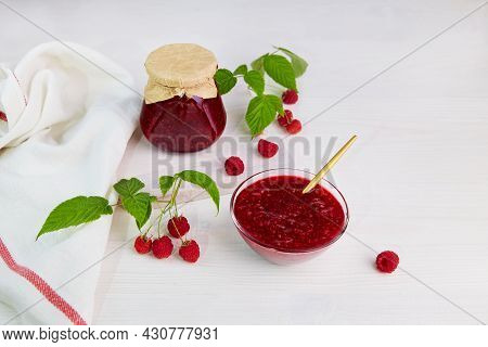 Raspberry Jam In A Glass Jar And Bowl. Conservation And Summer Harvest.