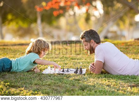 Strategic And Tactic. Tutorship. Dad And Kid Play Logic Game. Father And Son Playing Chess