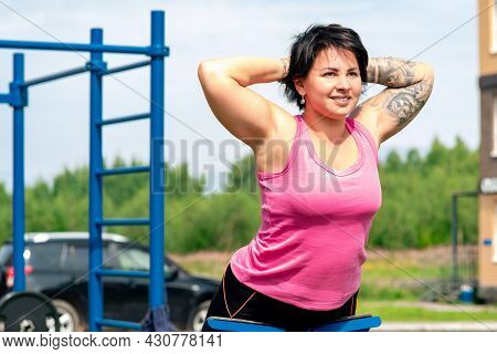 Young Woman Performing Back Extension Exercises Using An Outdoor Exercise Machine Hyper Extension Be