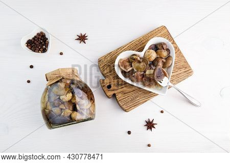 Pickled Mushrooms In A Glass Jar And Bowl On White Wooden Background. Homemade Food Preserving. Mari